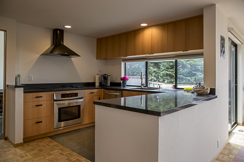 A view of the kitchen showing the stove and counter with a window looking out onto the garden.