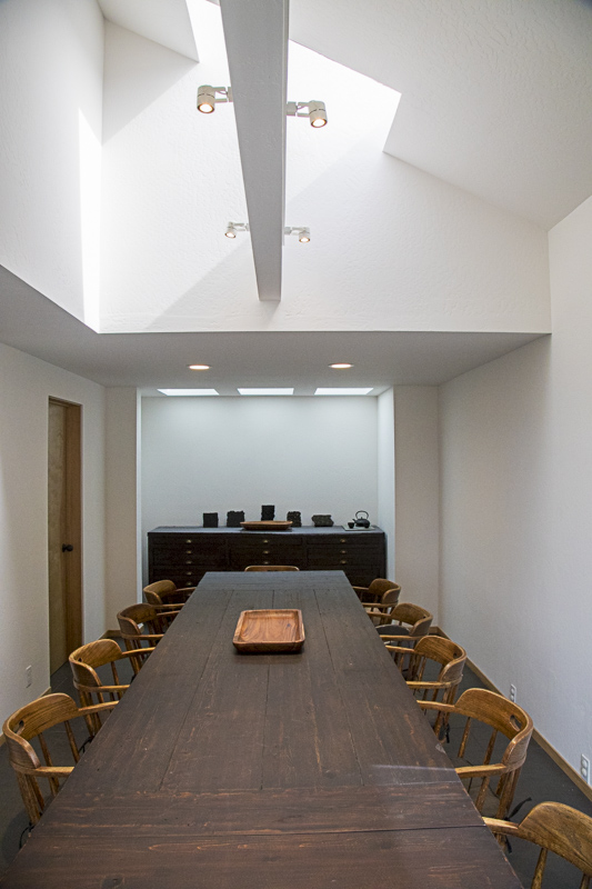 A conference room with ten chairs and two tables.