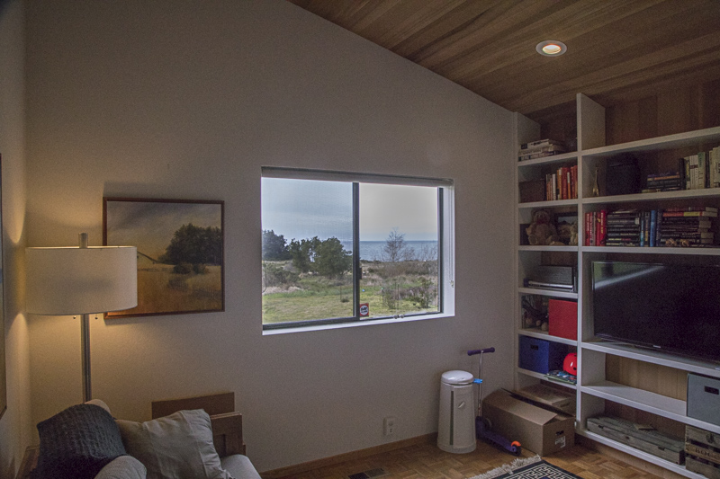 Interior of a room showing a bookcase, the corner of a couch, a lamp and a window looking past the meadow out to the ocean beyond.