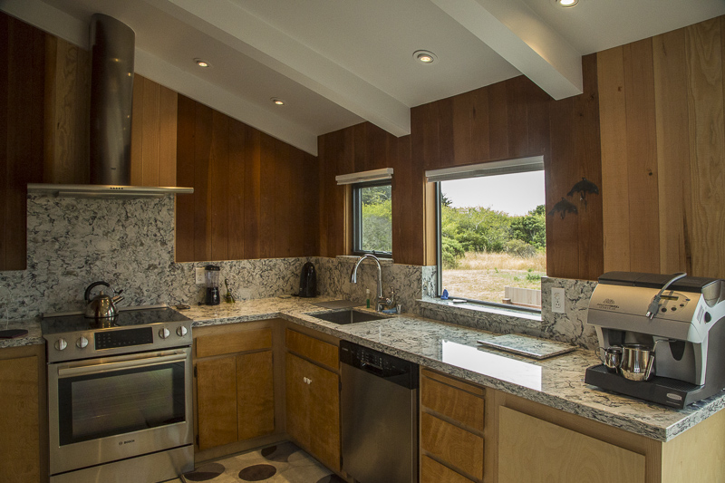 A kitchen showing the counter with sink, coffee maker, and stove with a view of the garden through a window.