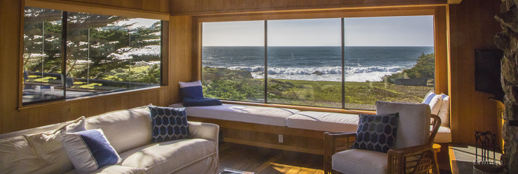 View of the ocean from inside a room with window seats, a sofa and a chair.