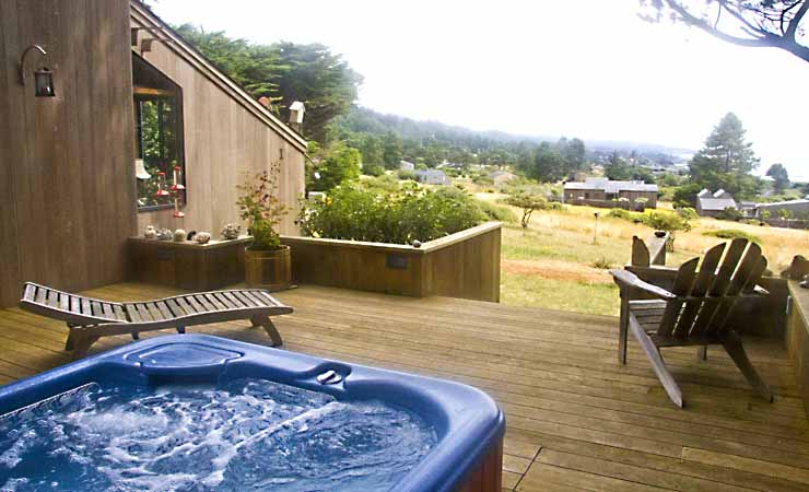 A deck next to a home with hot tub, chair, chiase, and view of the garden beyond the deck.