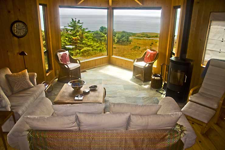 The interior of the living room show the view out of two large windows, a sofa, a love seat, three chairs and a table.