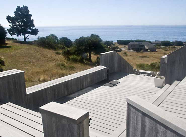 An exterior deck with a view of the ocean beyond the hillside.