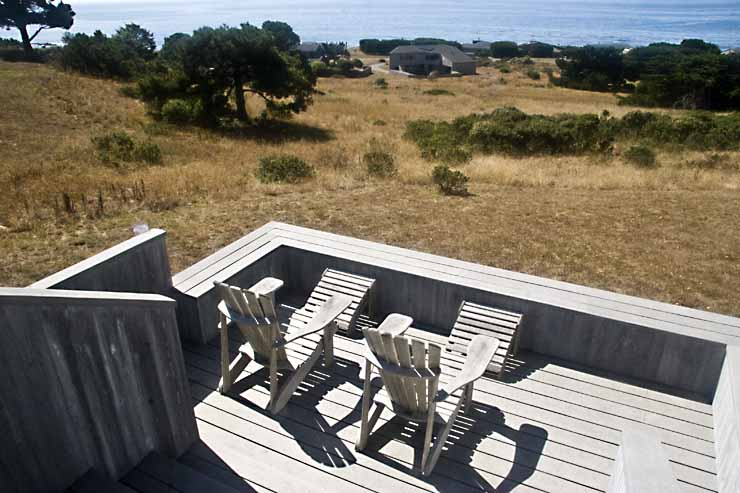 An exterior deck with two chairs and a view of the ocean beyond the hillside.