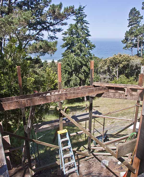 The framework of the old deck with a ladder and a view of the ocean beyond some trees.