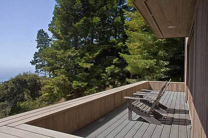 The finished deck with two chairs looking out past some trees to the ocean beyond.